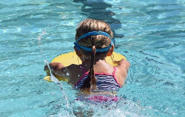 Une fille qui nage dans une piscine à l'aide d'une planche de natation.